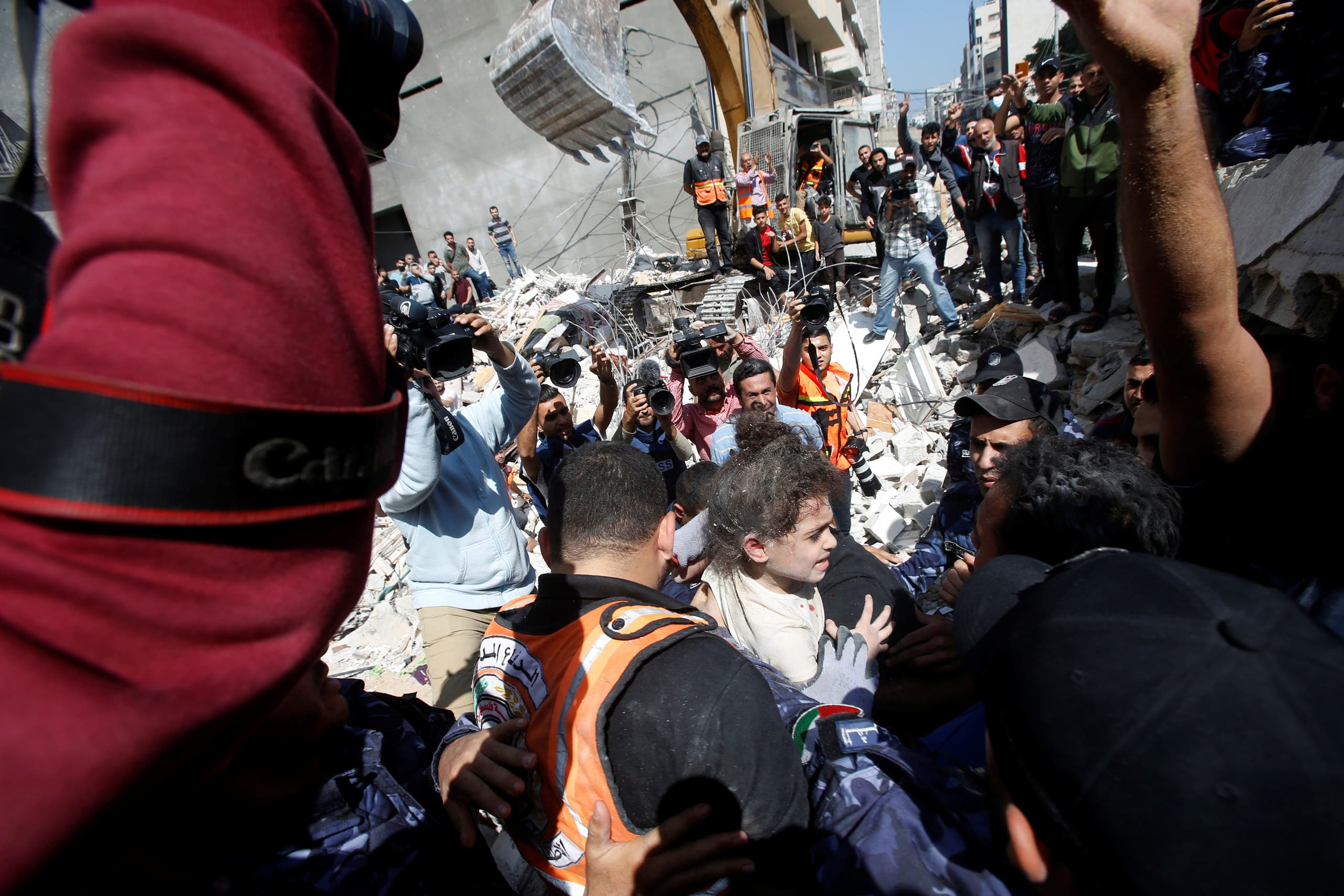 Rescuers carry Suzy Eshkuntana, 6, as they pull her from the rubble of a building at the site of Israeli air strikes, in Gaza City May 16, 2021. (Reuters)