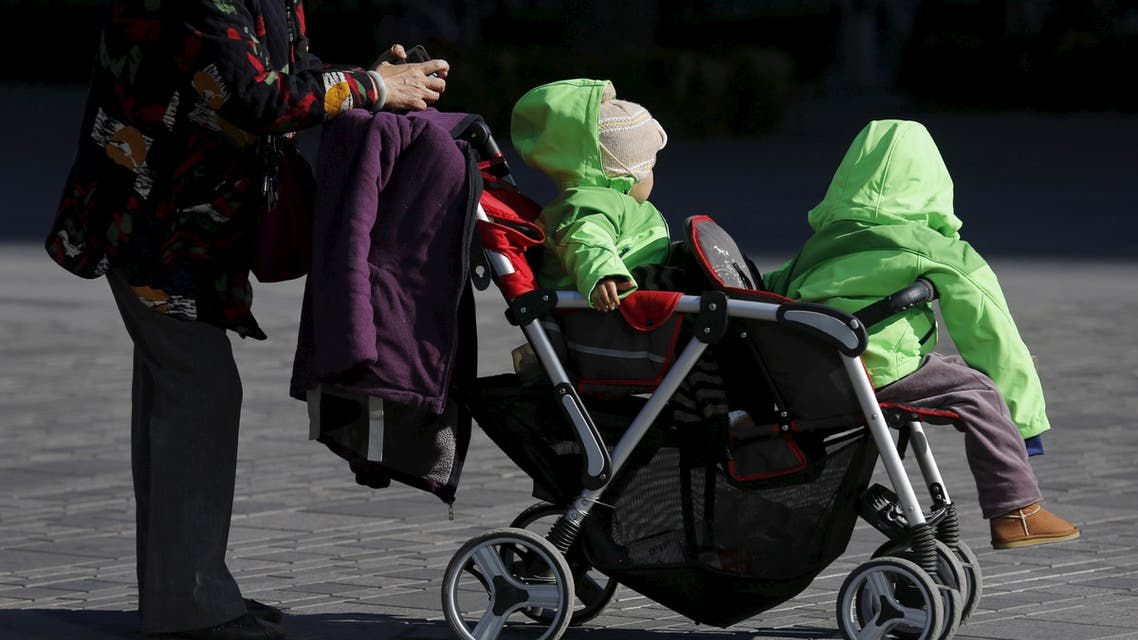 An elderly woman pushes two babies in a stroller in Beijing, October 30, 2015. (File photo: Reuters)