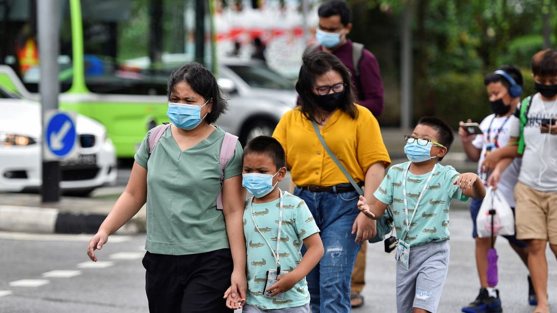 People wearing face masks cross a road amid the coronavirus disease (COVID-19) outbreak in Singapore May 14, 2021. (Reuters)
