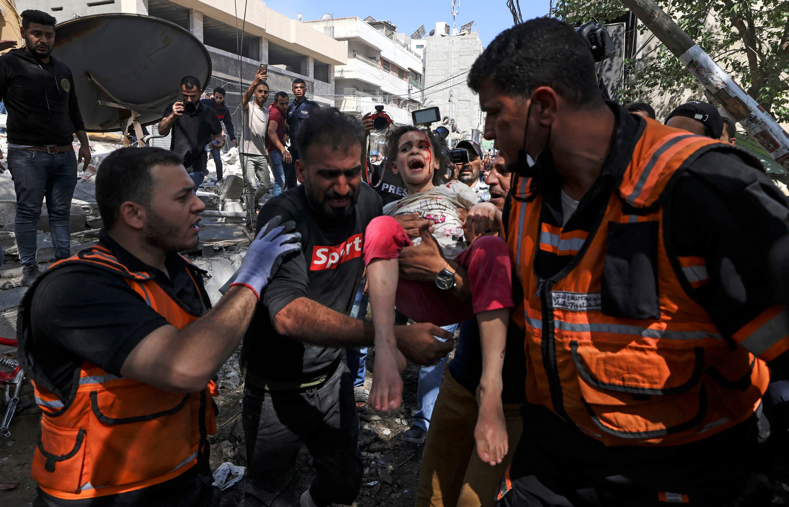 Palestinian paramedics evacuate a girl from the rubble of a destroyed building in Gaza City's Rimal residential district on May 16, 2021, following massive Israeli bombardment. (AFP)