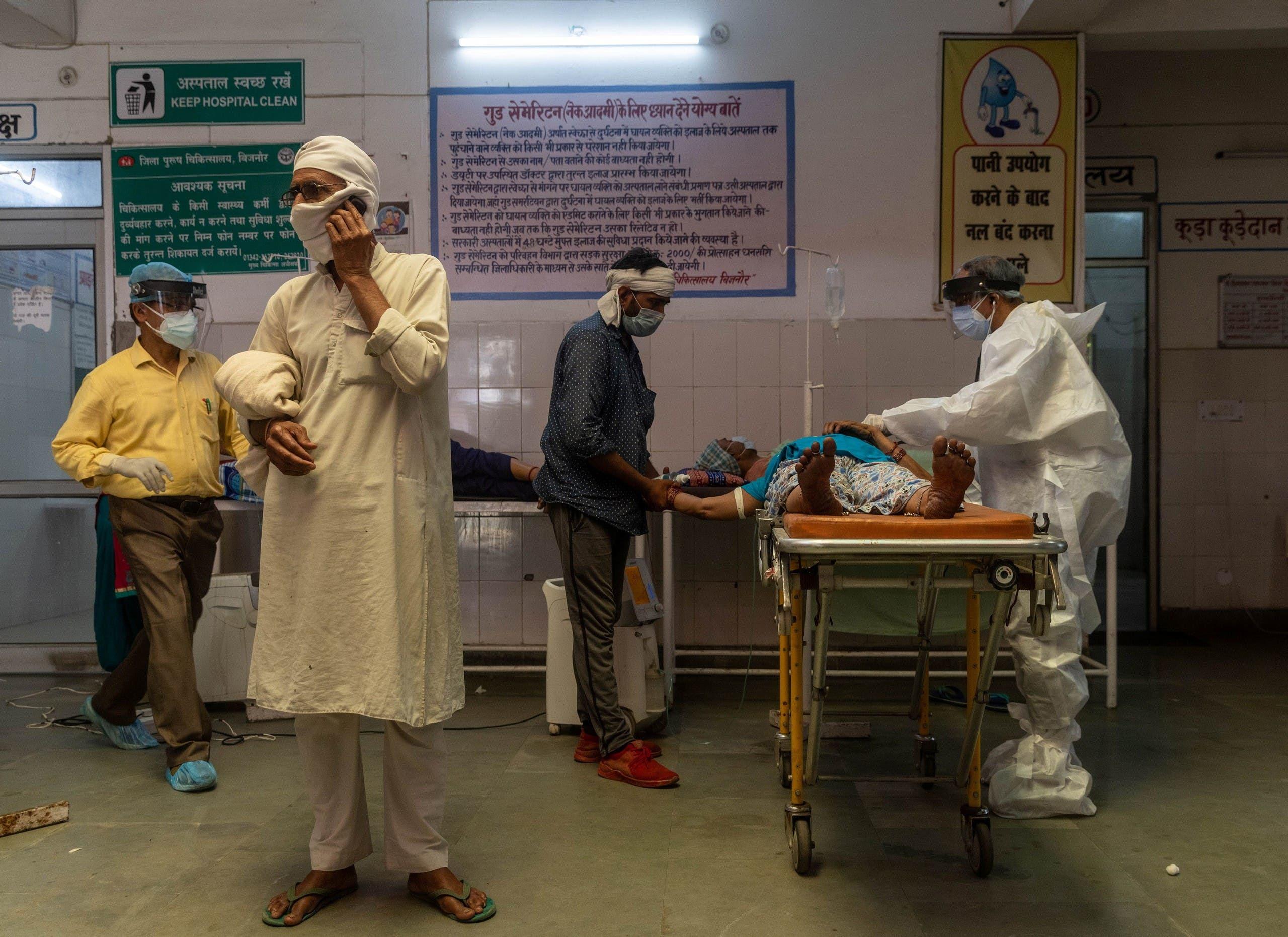 رجل يتحدث على الهاتف بينما تحاول طبيبة في أحد مستشفيات بجنور بالهند انعاش زوجته