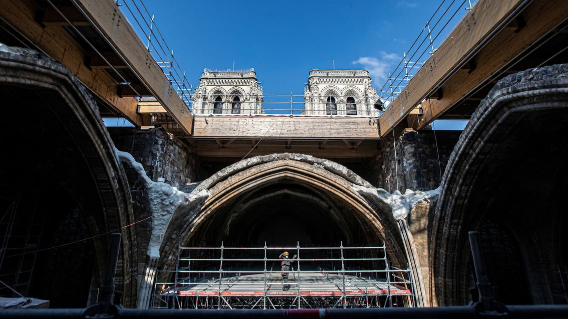 A workman stands on scaffolding under a vault at the reconstruction site during French President Emmanuel Macron's visit at the Notre-Dame de Paris Cathedral, which was damaged in a devastating fire two years ago, as restoration works continue, in Paris, France, April 15, 2021. (Reuters)