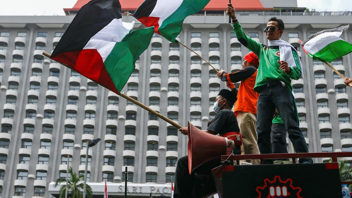 Members of Indonesian labour organizations wave Palestinian flags during a protest against Israel outside the United Nations building in Jakarta, Indonesia, May 18, 2021. (Reuters)