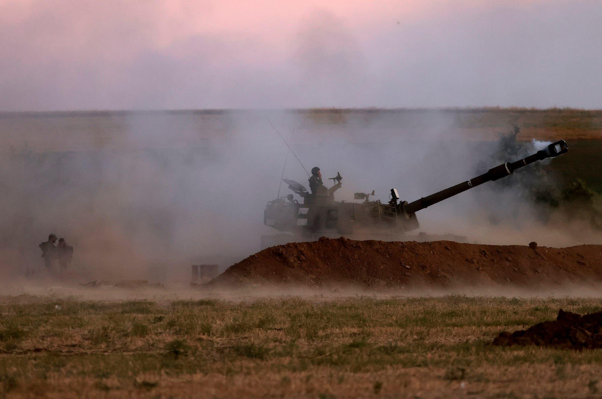 جنود إسرائيليون يطلقون قذيفة باتجاه قطاع غزة من موقعهم على طول الحدود يوم 18 مايو 2021 (فرانس برس)