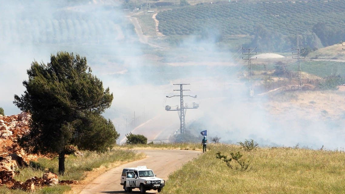 A UN peacekeeper (UNIFIL) stands as smoke rise in the southern Lebanese village of Khiam, near the border with Israel, Lebanon May 14, 2021. (Reuters)