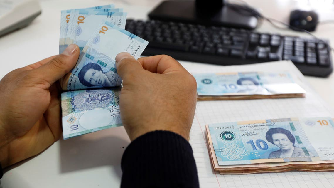 A man counts 10 Dinar banknotes depicting the country's first woman doctor, Tawhida Ben Cheikh, in Tunis, Tunisia. (File photo: Reuters)