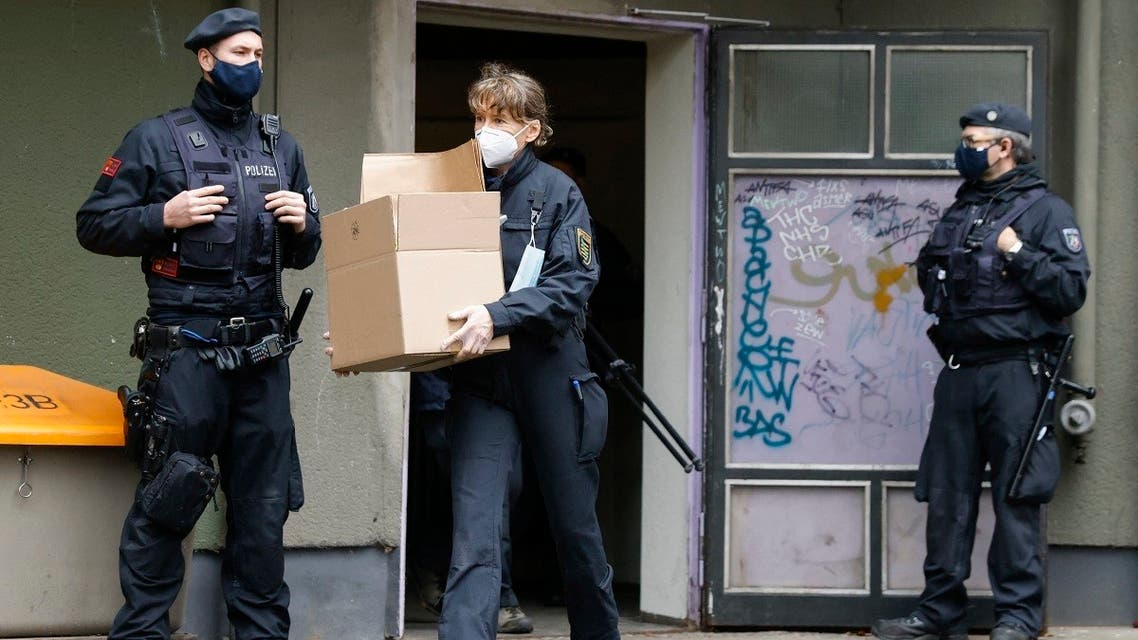 A policewoman carries box with evidence out of a building in Berlin's Kreuzberg district during raids of properties on November 17, 2020 in connection with a spectacular heist on Green Vault museum in Dresden's Royal Palace on November 25, 2019. (AFP)