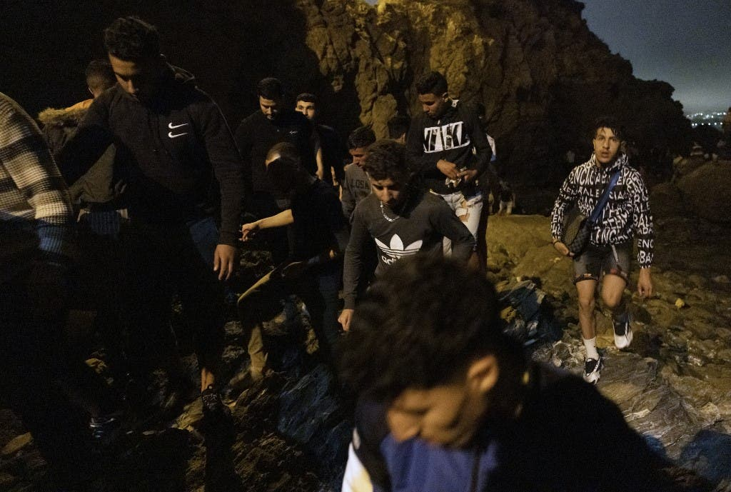 Moroccan migrants climb a cliffside on the shore of the northern town of Fnideq as they attempt to cross the border from Morocco to Spain's North African enclave of Ceuta on May 18, 2021(File photo: AFP)