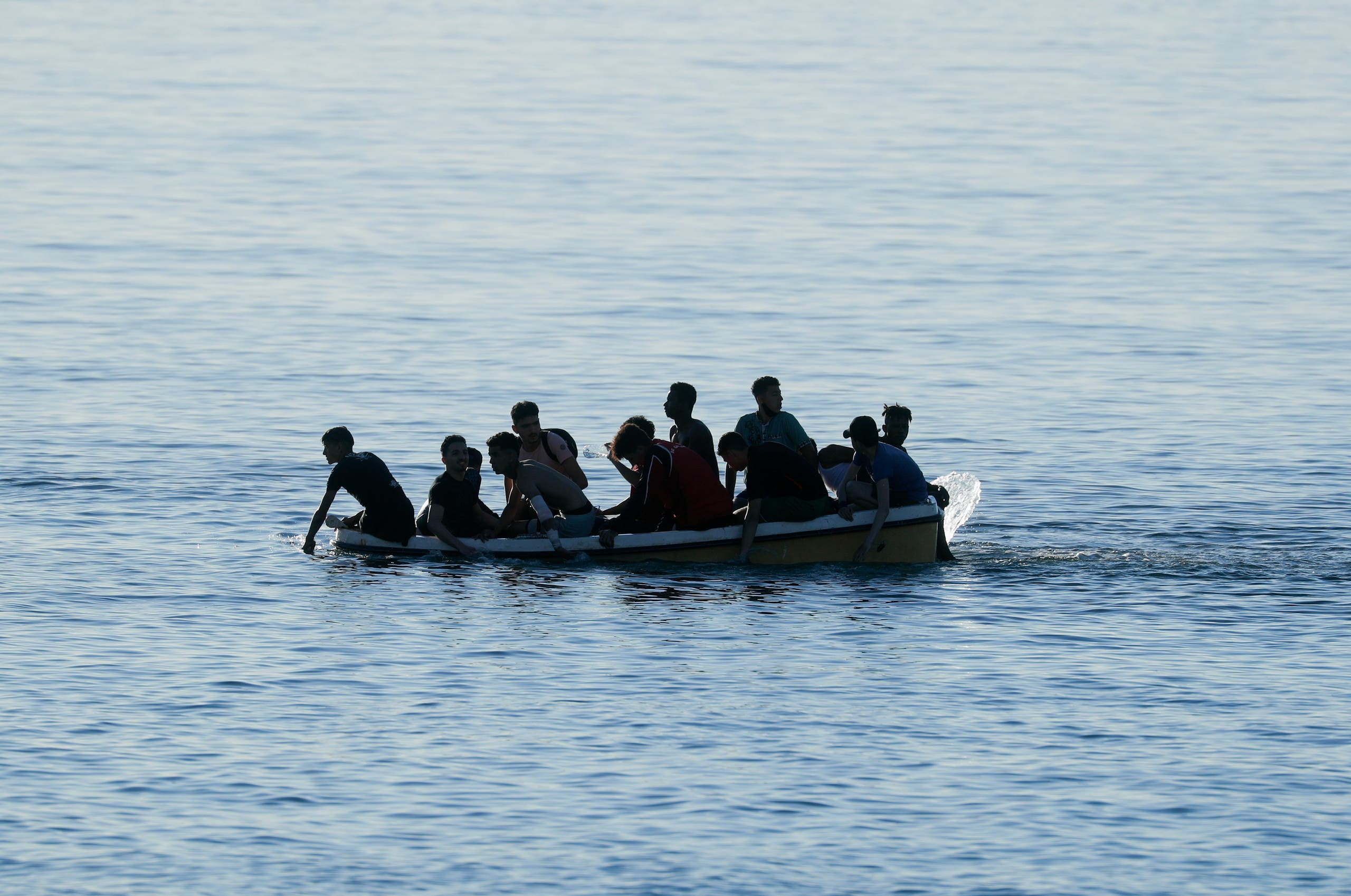 Moroccan citizens arrive on a boat at El Tarajal beach, near the fence between the Spanish-Moroccan border, after thousands of migrants swam across the border on Monday, in Ceuta, Spain, May 19, 2021. (Reuters)