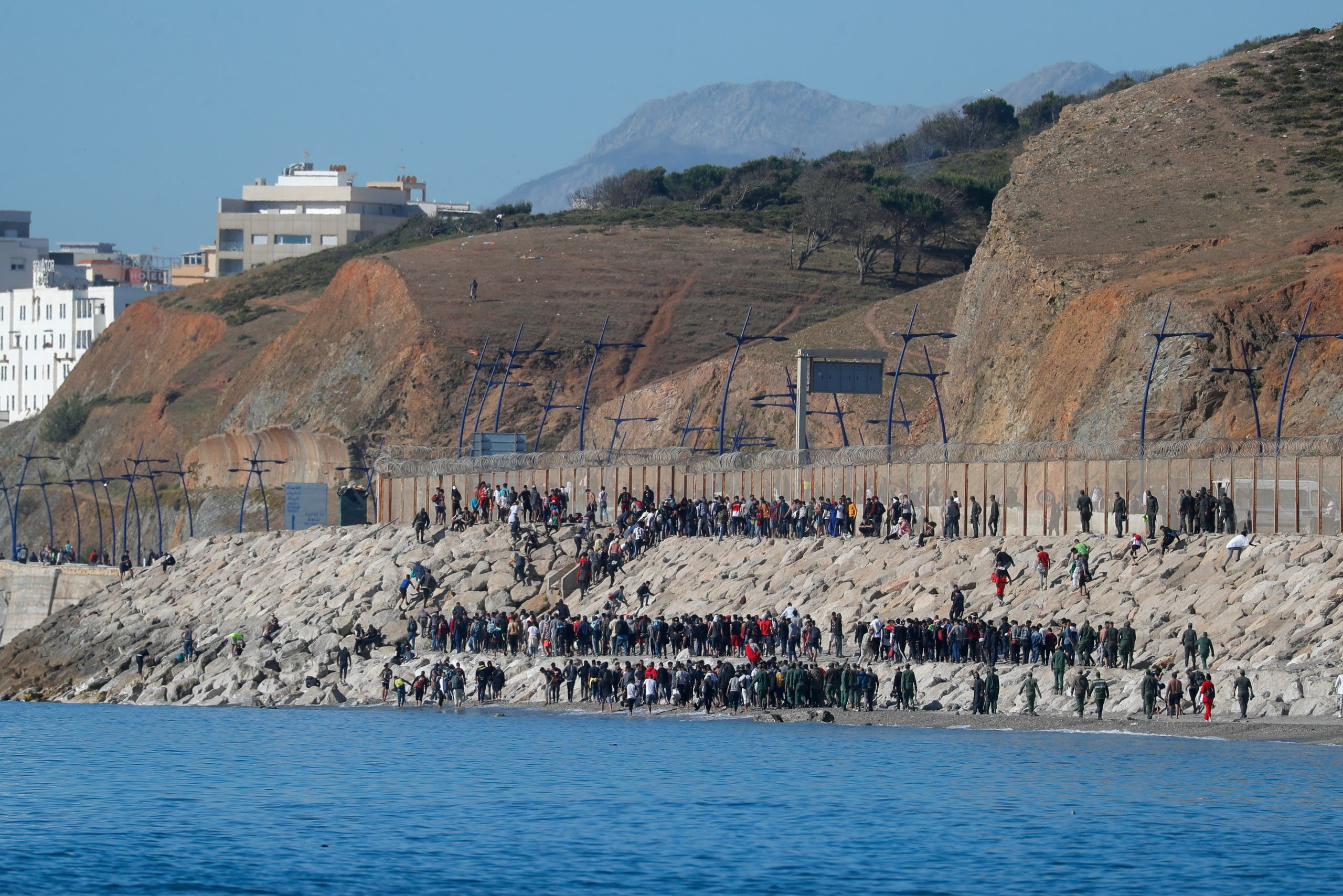 Migrants are led by Moroccan soldiers back to Morocco from El Tarajal beach, at the fence between the Spanish-Moroccan border, after thousands of migrants swam across the border, in Ceuta, Spain, May 19, 2021. (Reuters)