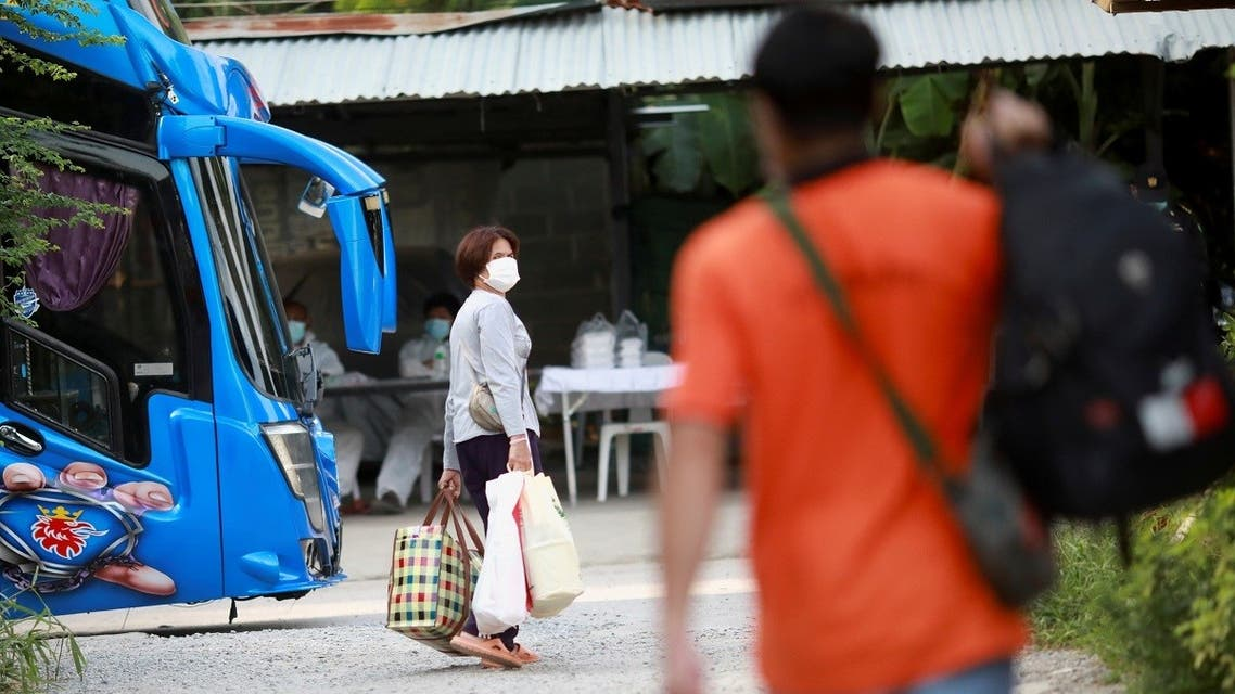 A woman who has tested positive for the coronavirus disease (COVID-19) walks towards a bus as she is sent to a hospital, in Bangkok, Thailand, on May 17, 2021. (Reuters)