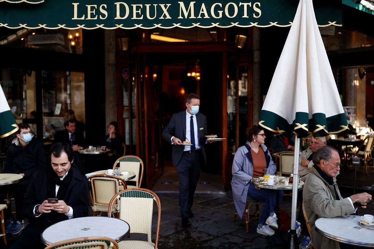 Customers sit on the terrace of the cafe and restaurant Les Deux Magots in Paris as cafes, bars and restaurants reopen after closing down for months amid the coronavirus disease (COVID-19) outbreak in France, on May 19, 2021. (Reuters)