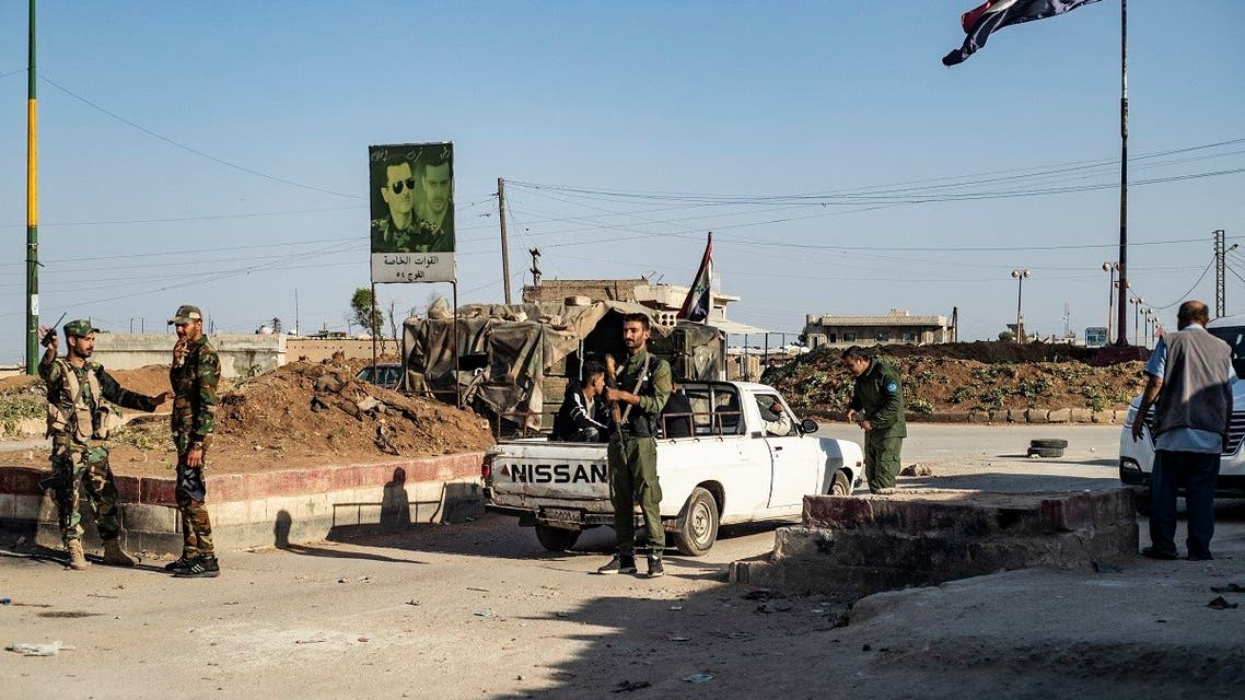 """Members of the Syrian Kurdish internal security services known as """"Asayish"""" and Syrian government forces man a checkpoint in the al-Tay neighborhood of Syria's northeastern city of Qamishli on April 27, 2021. (Delil Souleiman/AFP)"""