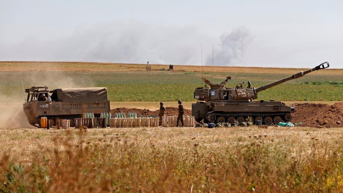 جنود إسرائيليون يطلقون قذيفة باتجاه قطاع غزة من موقعهم على طول الحدود يوم 19 مايو (فرانس برس)