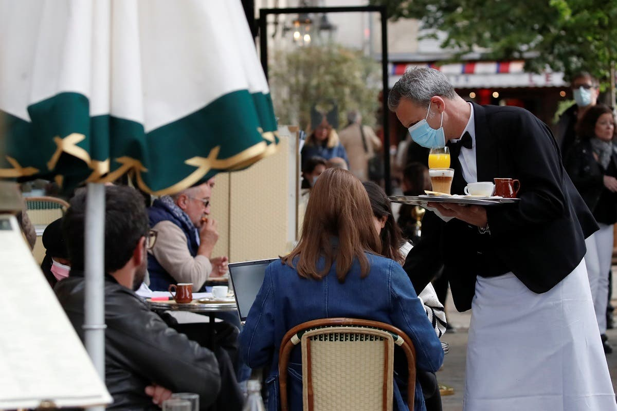 A waiter serves customers as cafes, bars and restaurants reopen their terraces after closing down for months, amid the coronavirus outbreak, in Paris, France, on May 19, 2021. (Reuters)