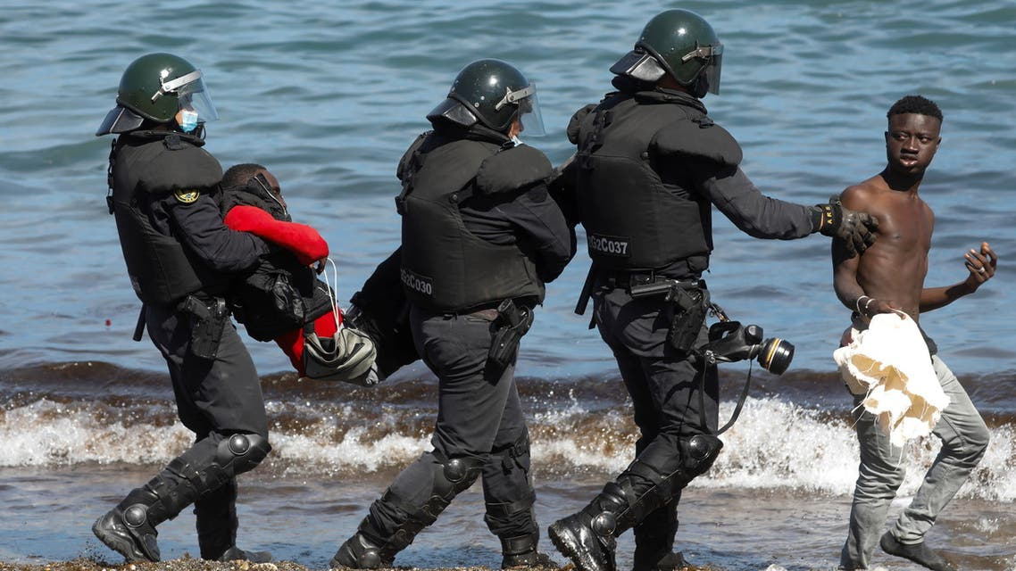 Spanish security forces members carry and escort Moroccan citizens at El Tarajal beach, near the fence between the Spanish-Moroccan border, after thousands of migrants swam across this border during last days, in Ceuta, Spain, May 18, 2021. (Reuters)