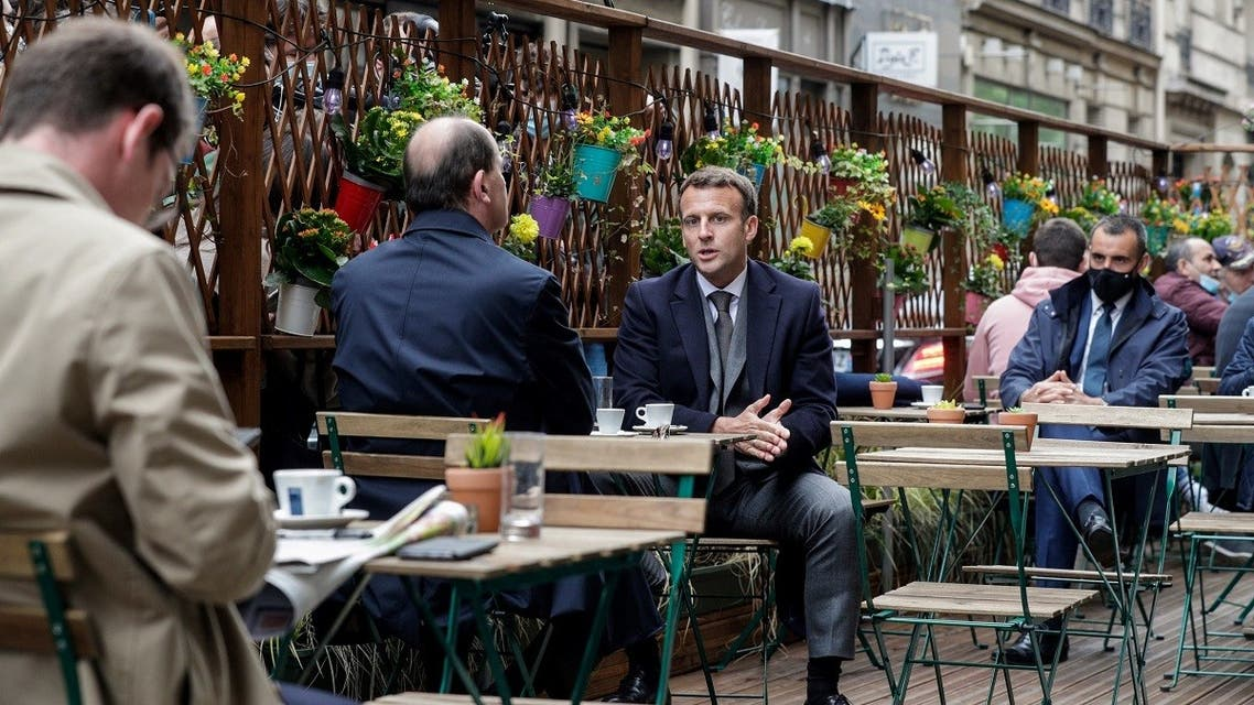 French President Emmanuel Macron (R) and French Prime Minister Jean Castex (L) are having coffees at a cafe terrace in Paris on May 19, 2021, as restaurant and bar terraces reopen today at 50-percent capacity for groups of up to six while the curfew will be pushed back from 7 to 9:00 pm. (AFP)