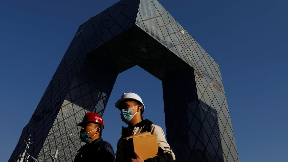 People wearing face masks following the coronavirus disease (COVID-19) outbreak walk past the CCTV headquarters, the home of Chinese state media outlet CCTV and its English-language sister channel CGTN, in Beijing, China February 5, 2021. (Reuters)