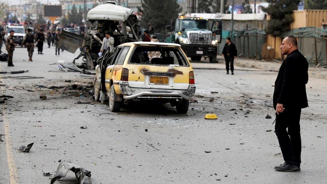 Afghan officials inspect a damaged minibus after a blast in Kabul, Afghanistan, on March 15, 2021. (Reuters)