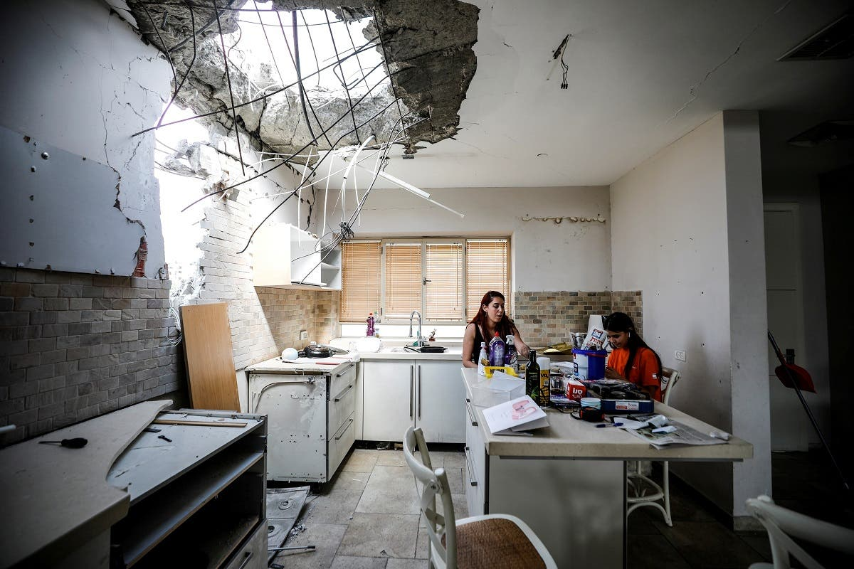 Family members of the Vaizel family, sit in the kitchen of their house which was damaged after it was hit by a rocket launched from the Gaza Strip earlier this week, in Ashkelon, Israel May 20, 2021. (Reuters)