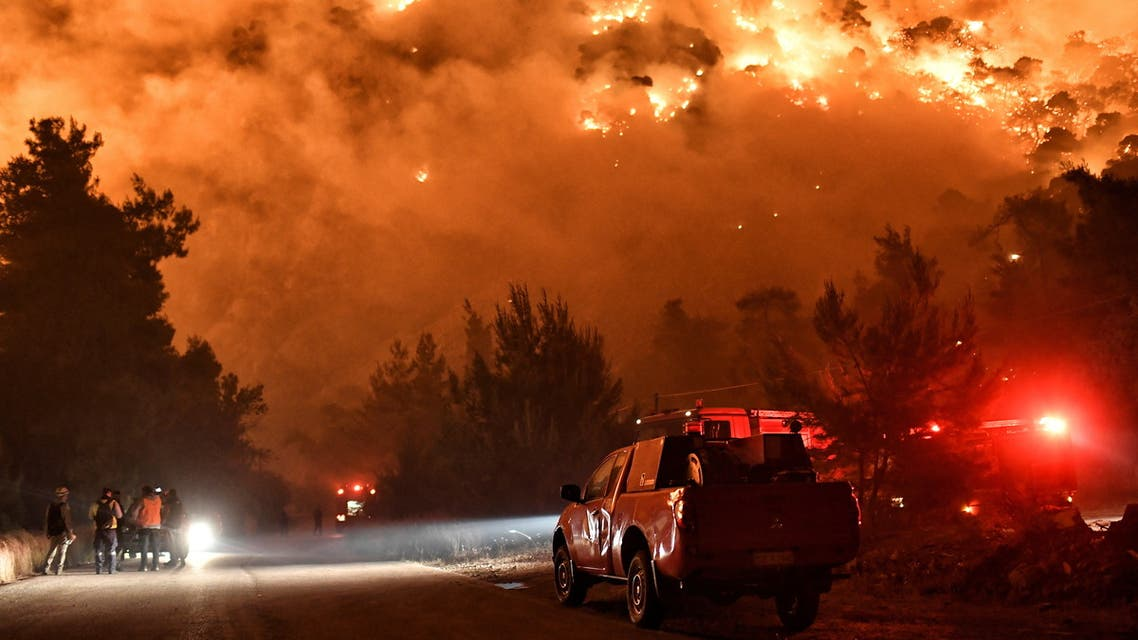 Flames rise as firefighters and volunteers try to extinguish a fire burning in the village of Schinos, near Corinth, Greece, May 19, 2021. Picture taken May 19, 2021. REUTERS/Vassilis Psomas