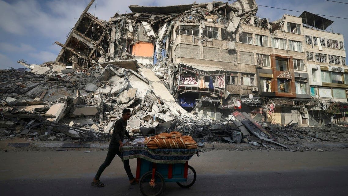 A Palestinian man walks past the destroyed Al-Shuruq building in Gaza City on May 20, 2021 after it was bombed by an Israeli air strike. (AFP)