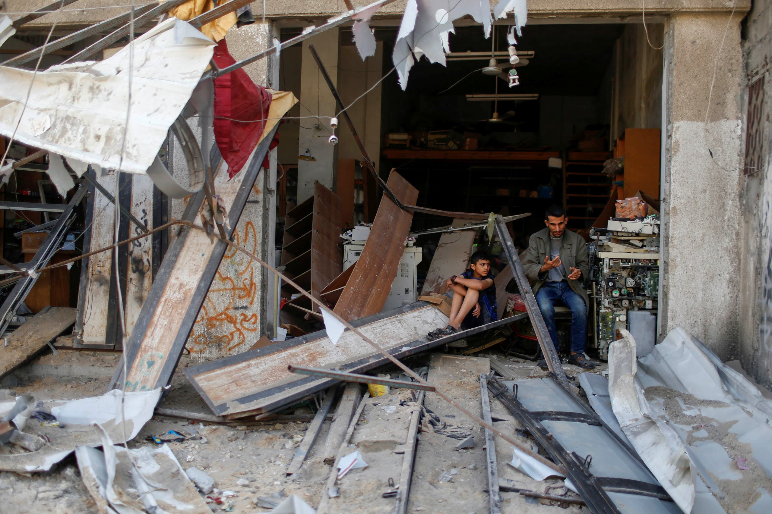 Palestinians sit amidst the damage in the aftermath of Israeli air strikes, amid Israeli-Palestinian fighting, in Gaza, May 20, 2021. (Reuters)