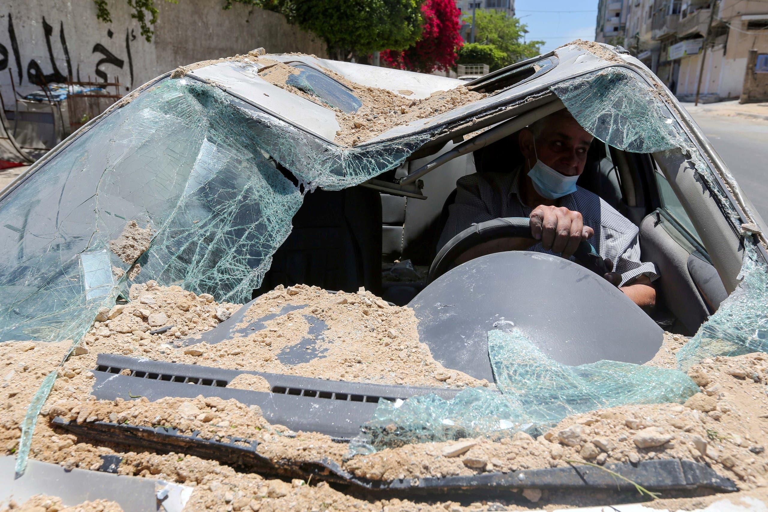 فلسطيني داخل سيارته التي دمرها القصف الإسرائيلي على غزة