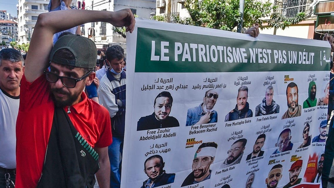 Algerians hold signs with portraits of activists held in jail, during an anti-government demonstration in the capital Algiers on May 7, 2021. (AFP)