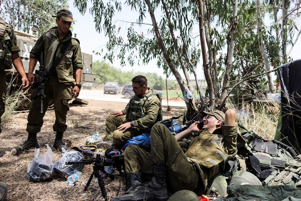 sraeli soldiers sit together in a field near the border between Israel and the Gaza Strip, on its Israeli side, following Israel-Hamas truce May 21, 2021.  (Reuters)