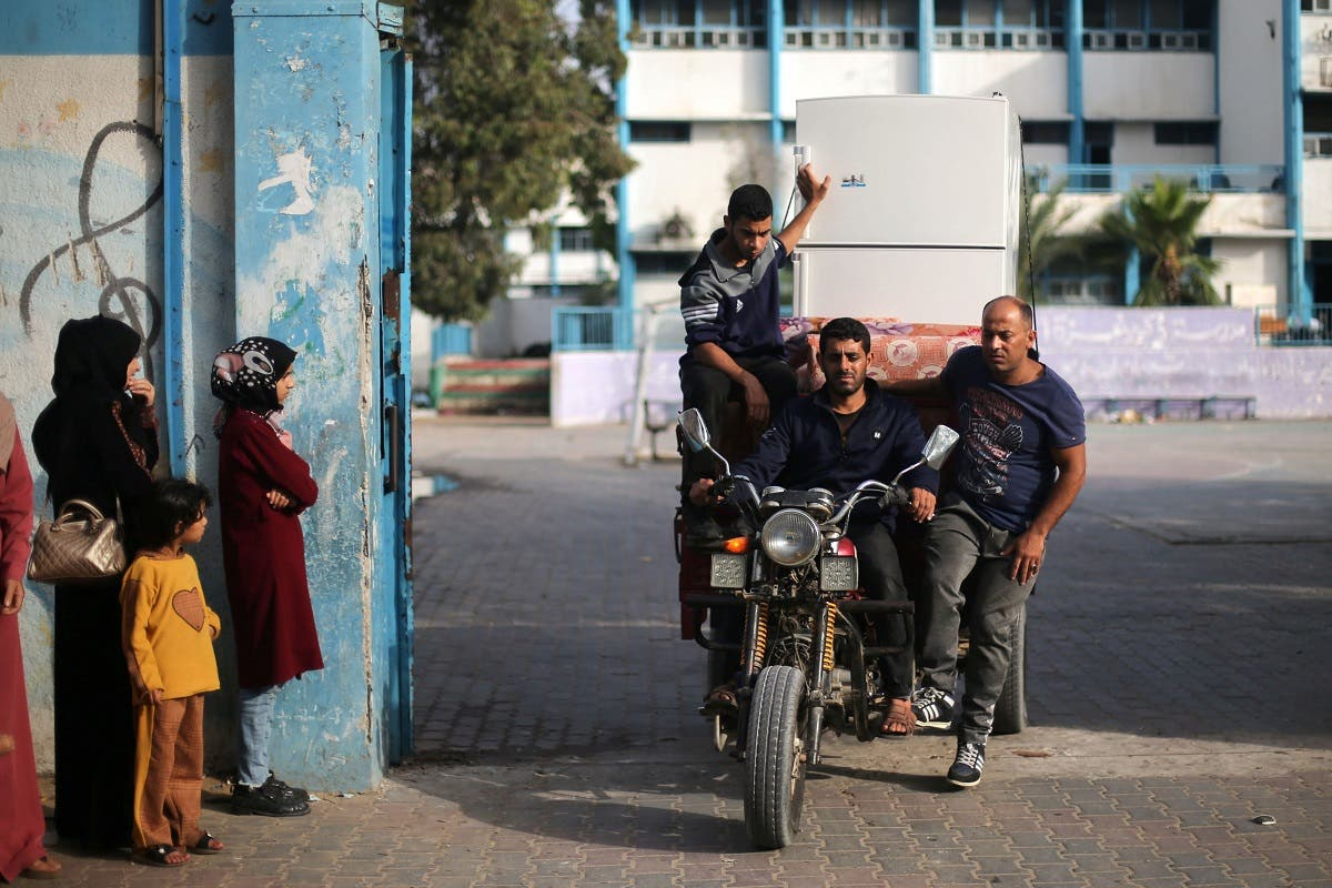 Palestinians riding on an auto rickshaw loaded with belongings head to their home as they leave a United Nations-run school where they took refuge during the recent cross-border violence between Palestinian militants and Israel, following Israel-Hamas truce, in Gaza May 21, 2021. (Reuters)
