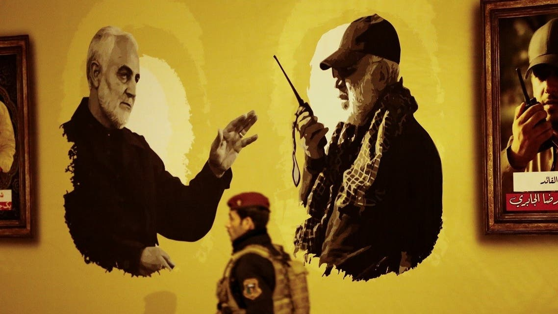 A fighter from Hashid Shaabi (Popular Mobilization Forces) walks in front of a banner during the first anniversary of the killing of senior Iranian military commander General Qassem Soleimani and Iraqi militia commander Abu Mahdi al-Muhandis in a U.S. attack, at Baghdad airport, Iraq, January 2, 2021. (Reuters)