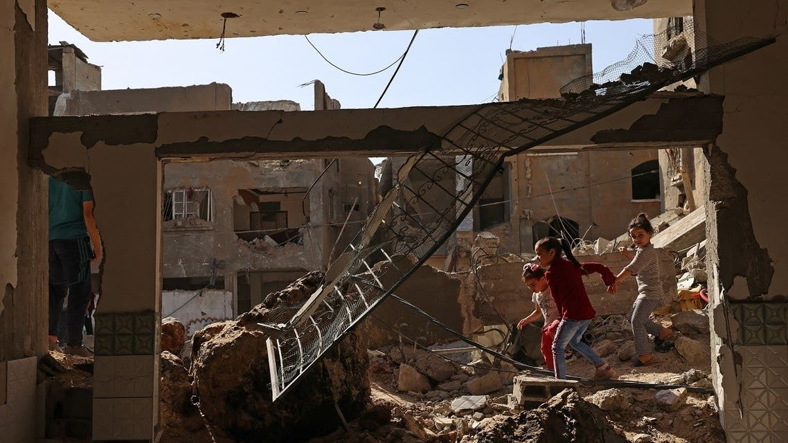 Palestinian children walk amidst the rubble of buildings, destroyed by Israeli strikes, in Beit Hanun in the northern Gaza Strip on May 21, 2021. (Reuters)