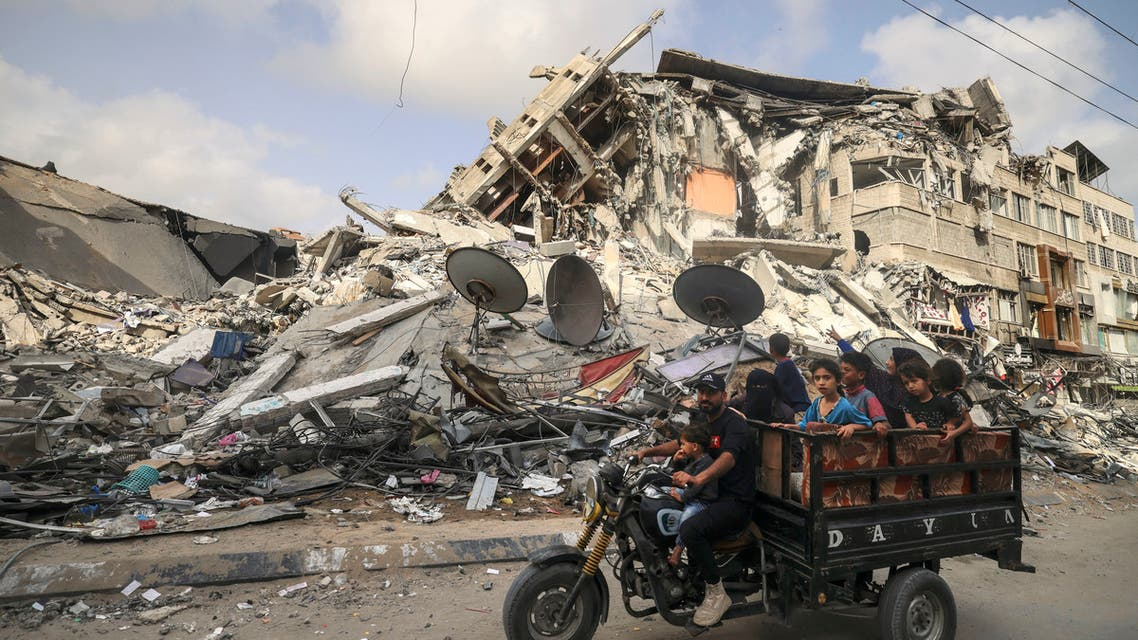 A Palestinian man transports children in a tricycle past the Al-Shuruq building, destroyed by an Israeli air strike, in Gaza City on May 21, 2021, after a ceasefire has been agreed between Israel and Hamas. A ceasefire between Israel and Hamas, the Islamist movement which controls the Gaza Strip, appeared to hold today after 11 days of deadly fighting that pounded the Palestinian enclave and forced countless Israelis to seek shelter from rockets.