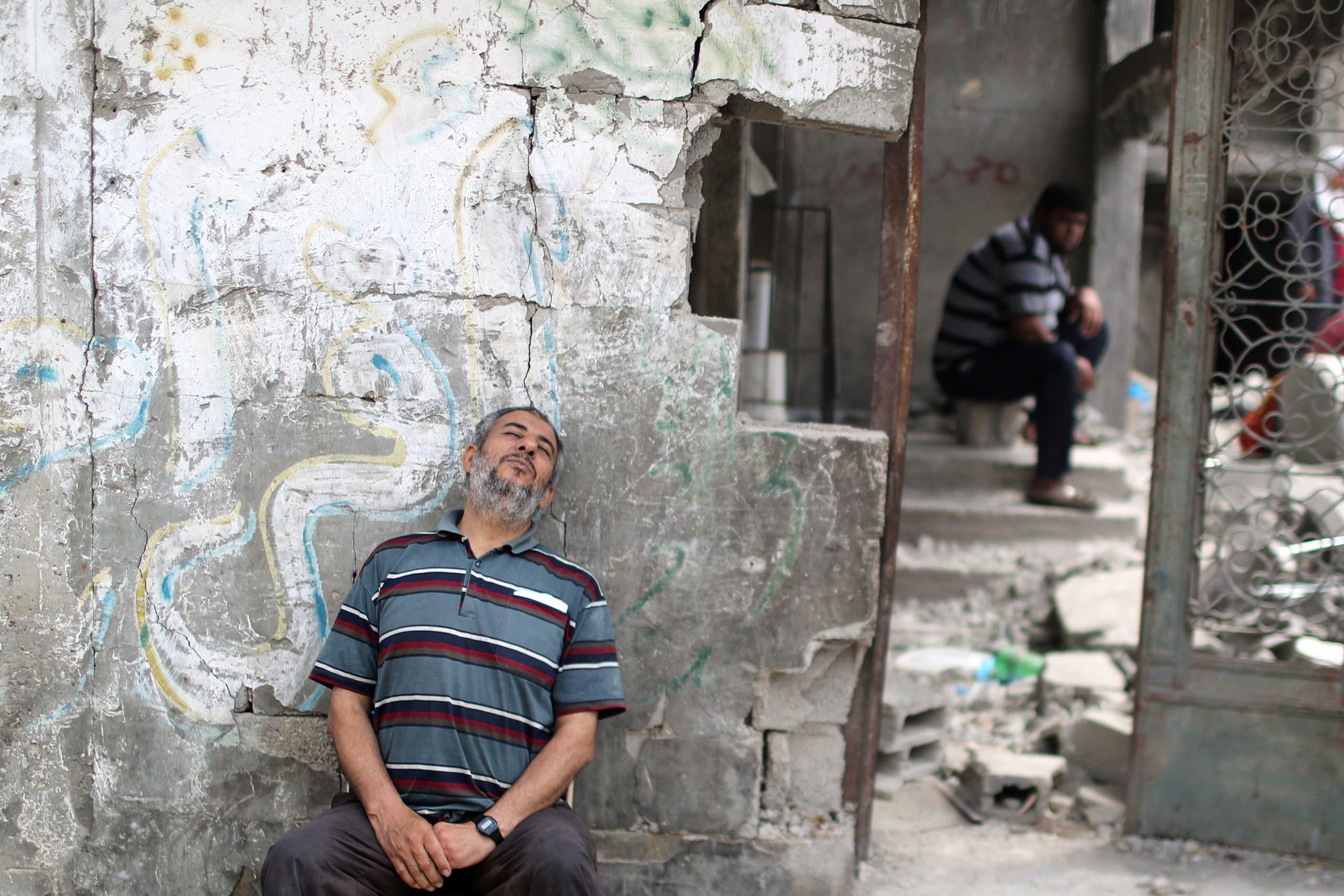 فلسطيني يجلس بجانب حطام منزله في غزة