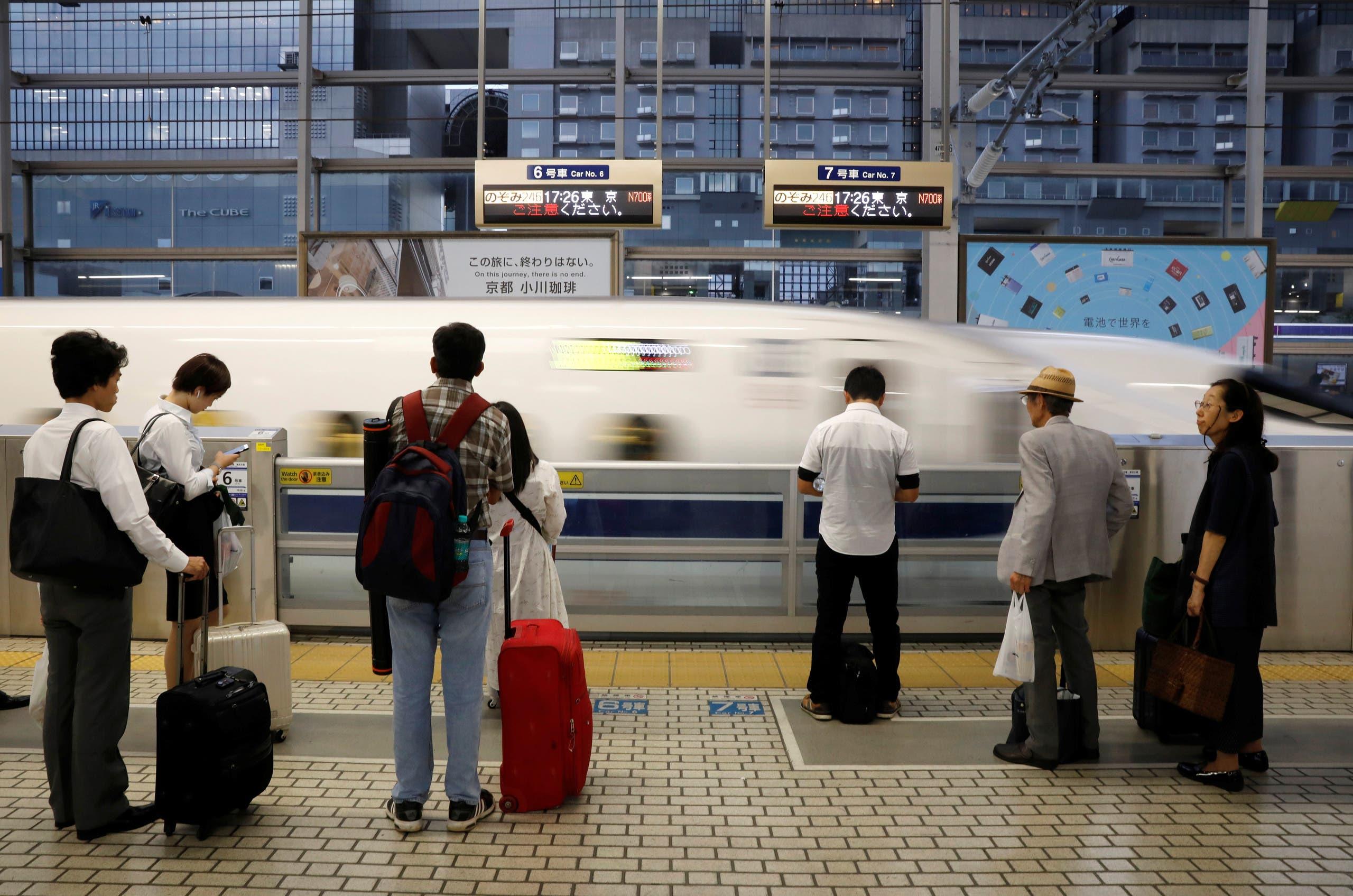 """مسافرون في محطة في كيوتو ينتظرون قطار الـ""""شينكانسن"""""""
