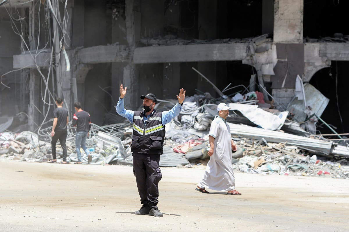 A Palestinian policeman directs traffic near a building damaged in Israeli missile strikes in the recent cross-border violence between Palestinian militants and Israel, following Israel-Hamas truce, in Gaza City May 21, 2021. (Reuters)