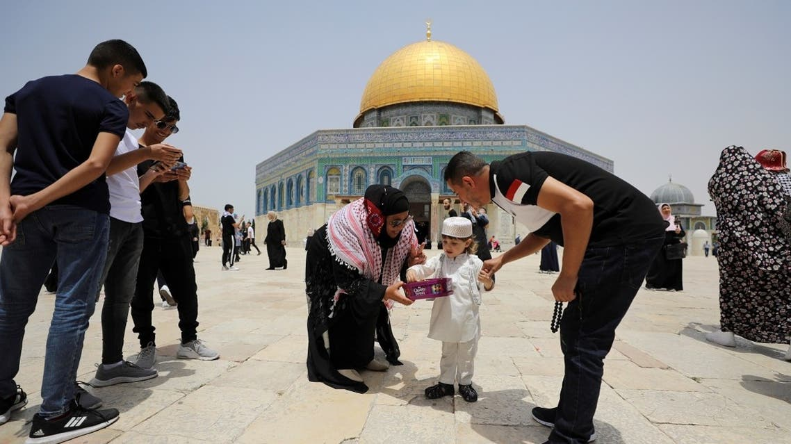 A Palestinian woman offers sweets to a boy before Friday prayer at at the compound that houses Al-Aqsa Mosque, known to Muslims as Noble Sanctuary and to Jews as Temple Mount, in Jerusalem's Old City May 21, 2021. (Reuters)