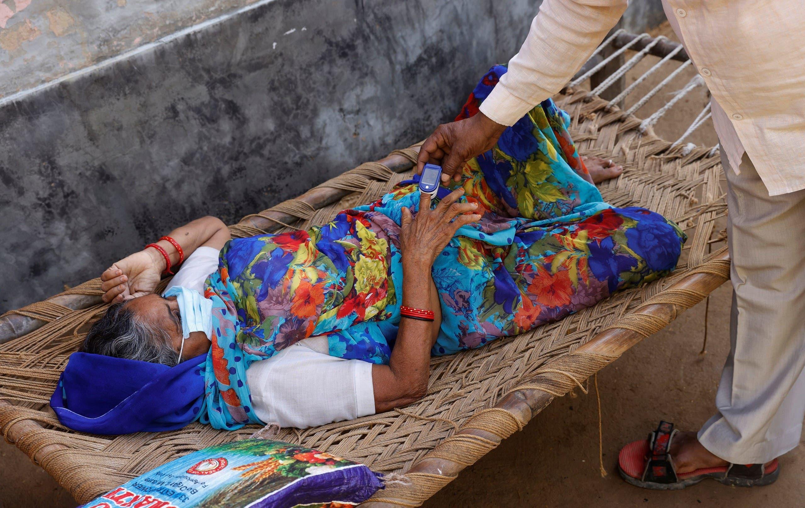 مسنة مصابة بكورونا في إحدى القرى الهندية تتلقى رعاية طبية