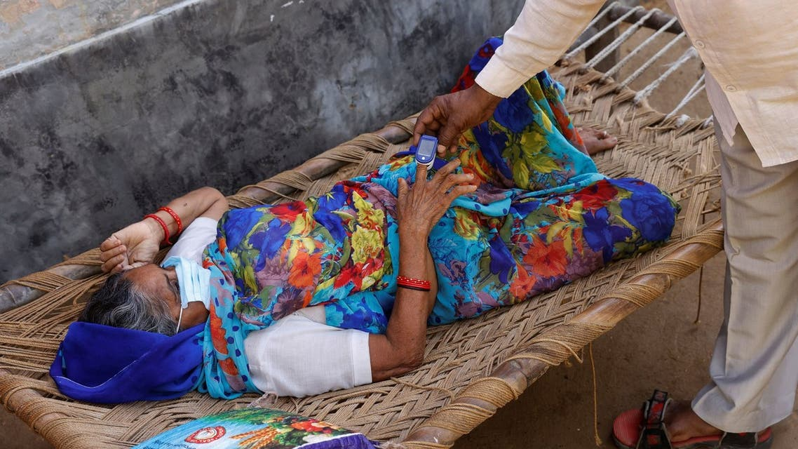 Moorti, 62, a villager suffering from fever rests on a cot as she waits to receive treatment at a clinic set up by a local villager, amidst the spread of the coronavirus disease (COVID-19), in Parsaul village in Greater Noida, in the northern state of Uttar Pradesh, India, May 22, 2021. REUTERS/Adnan Abidi