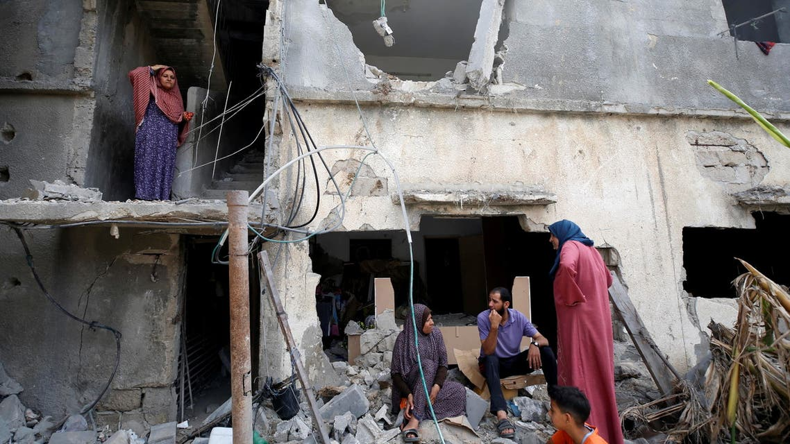 Palestinians sit on the debris after returning to their destroyed house following Israel- Hamas truce, in Beit Hanoun in the northern Gaza Strip, May 21, 2021. (Reuters)