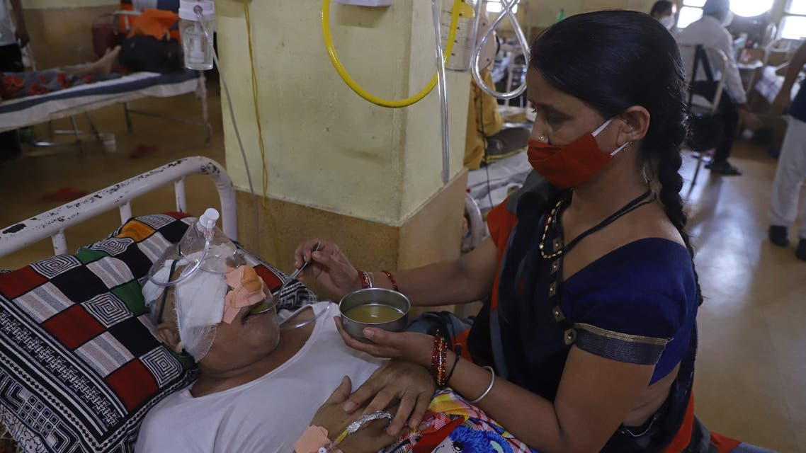 An attendant is seen next to a patient who recovered from the Covid-19 coronavirus and now infected with Black Fungus, a deadly fungal infection at the Netaji Subhash Chandra Bose Medical College in Jabalpur on May 21, 2021.