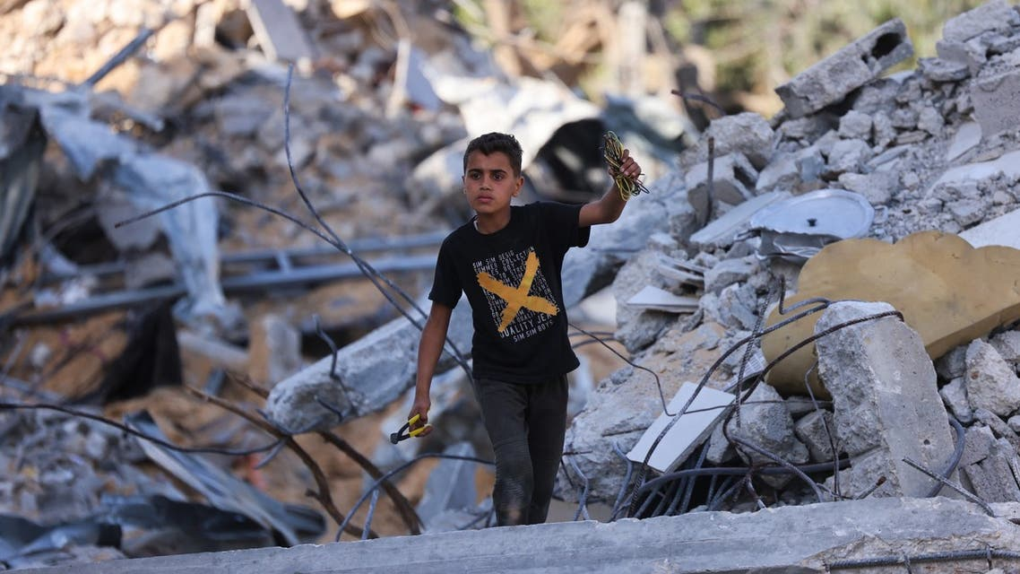 A Palestinian boy inspects the rubble of buildings, destroyed by Israeli strikes, in Beit Lahia in the northern Gaza Strip on May 21, 2021. A ceasefire in the conflict between Israel and Palestinian militants in the Gaza Strip, controlled by Islamist group Hamas, came into effect after 11 days of airstrikes and rocket fire.