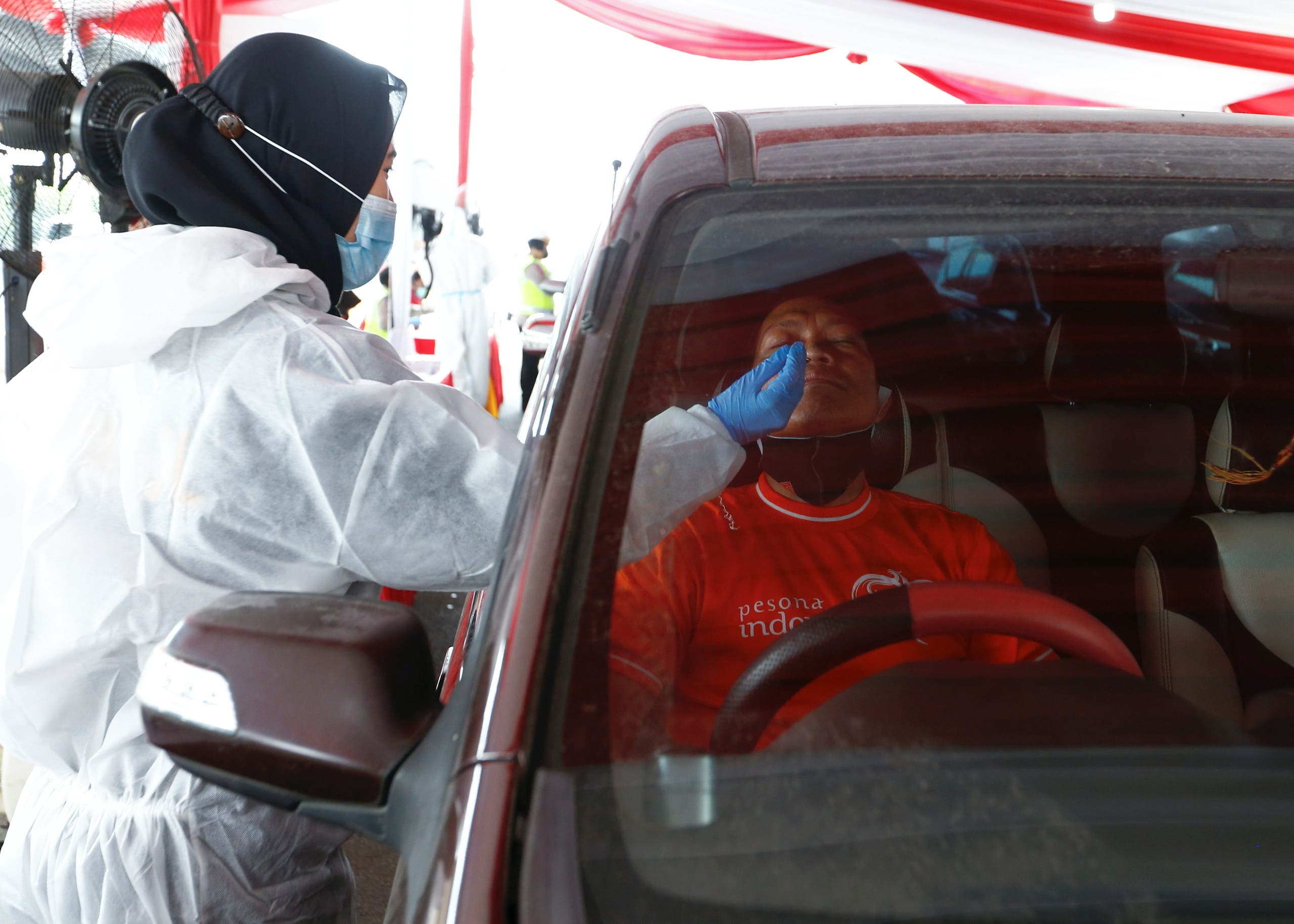 A healthcare worker in personal protective equipment takes a swab sample from a person to be tested for COVID-19 as travellers return to the capital city after the Eid al-Fitr festival, amid the coronavirus disease (COVID-19) pandemic, in Cikarang, Bekasi, on the outskirts of Jakarta, Indonesia, May 17, 2021. (Reuters)
