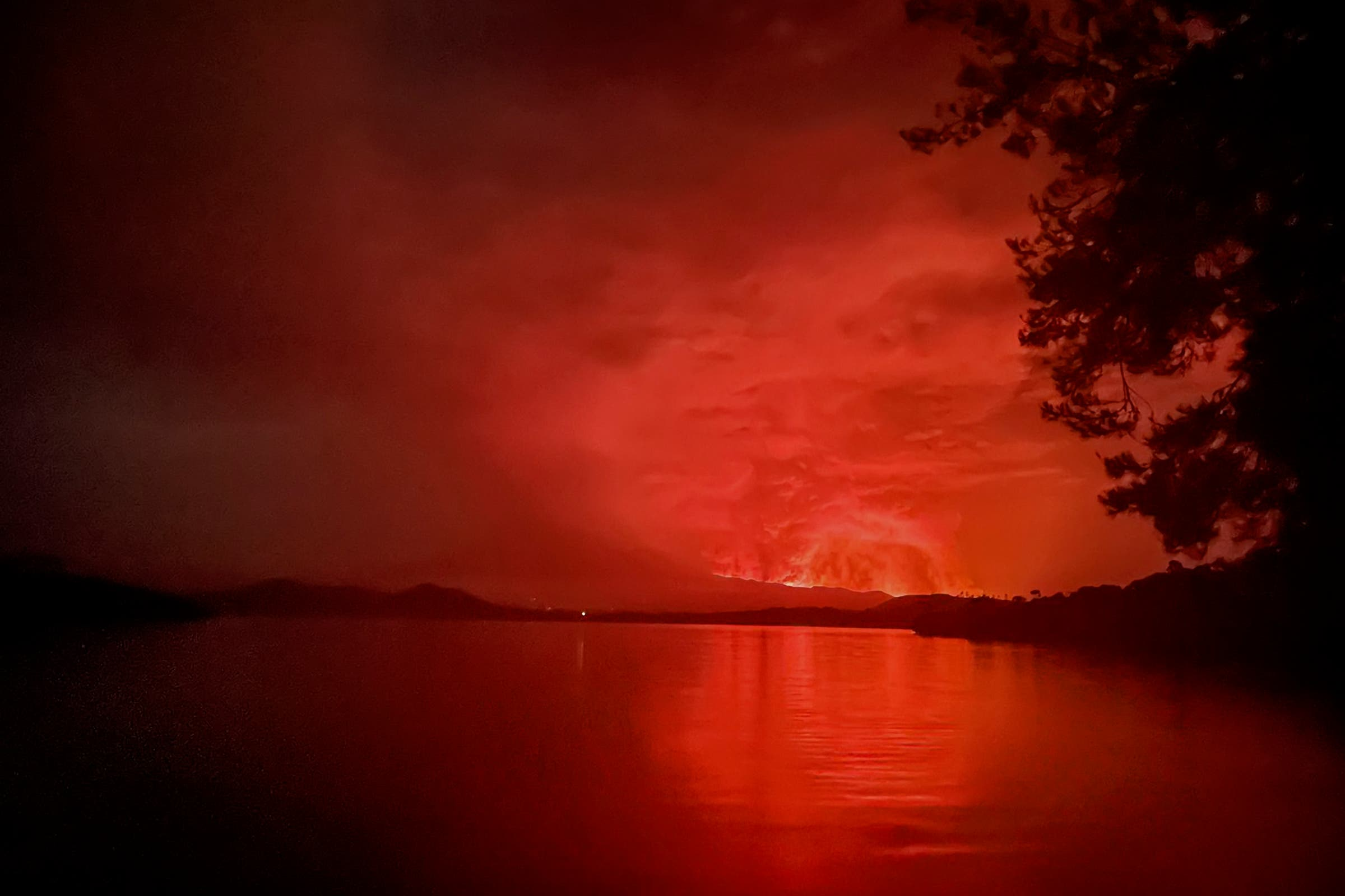 This general view taken on May 22, 2021 from Tchegera Island outsoide Goma on the lake Kivu in the East of the Democratic Republic of Congo shows flame spewing from the Nyiragongo volcano. (AFP)