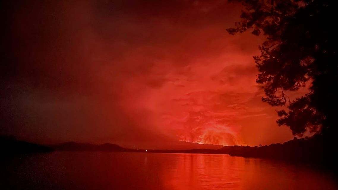 This general view taken on May 22, 2021 from Tchegera Island outsoide Goma on the lake Kivu in the East of the Democratic Republic of Congo shows flame spewing from the Nyiragongo volcano. The famous Nyiragongo volcano, near the city of Goma, in the east of the Democratic Republic of the Congo (DRC), suddenly became active on Saturday evening, an AFP correspondent noted. Strong emanations of glowing light coming out of the crater were visible from Goma, while a smell of sulfur was perceptible in the city, located on the southern flank of the volcano, on the shores of Lake Kivu, he noted. (AFP)