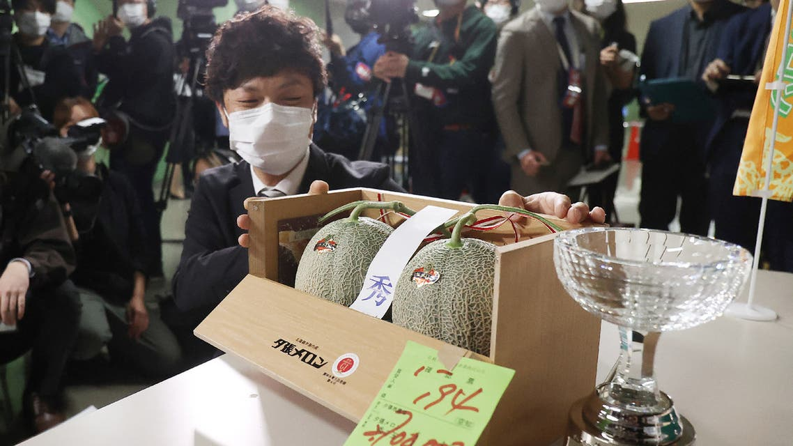 A man shows a pair of Yubari Melons which was sold for 2.7 million yen (about 25,000 USD) during the season's first auction at Sapporo Central Wholesale Market in Sapporo City, Hokkaido Prefecture on May 24, 2021. (AFP)