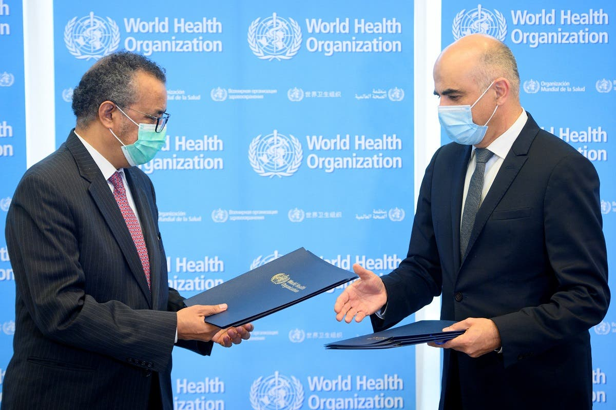Swiss Interior and Health Minister Alain Berset (R) exchanges documents with World Health Organization (WHO) Director General Tedros Adhanom Ghebreyesus during a bilateral meeting on the sidelines of the opening of the 74th World Health Assembly at the WHO headquarters, in Geneva, Switzerland, on May 24, 2021. (Reuters)