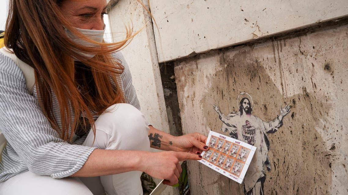 Artist Alessia Babrow shows the Vatican stamps during an interview with the Associated Press, at the Vatican, Friday, May 14, 2021. Babrow sued the Vatican City State's telecommunications office in a Rome court last month, saying it was wrongfully profiting off her creativity and violating the original intent of her artwork. The lawsuit, which is seeking nearly 130,000 euro in damages, said the Vatican had ignored Babrow's attempts to negotiate a settlement after she discovered it had reproduced her poster art unlawfully. (AP)