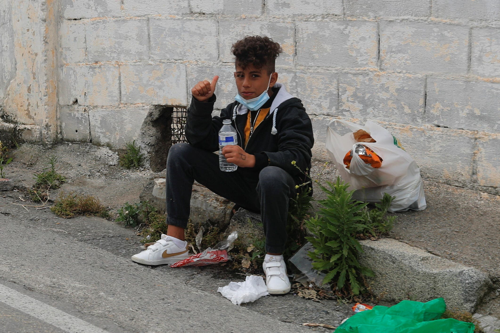 A migrant minor sits by the road after refusing to enter a facility prepared for migrants, near the Spanish-Moroccan border, after thousands of migrants swam across this border during the last days, in Ceuta, Spain, May 21, 2021. (Reuters/Jon Nazca)
